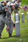 """Soldiers place American flags in front of headstones during """"Flags In"""" at Arlington National Cemetery in Arlington, Va., May 26, 2016. DoD photo by Marvin D. Lynchard"""