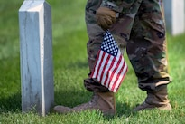 """A soldier places an American flag in front of a headstone during """"Flags In"""" at Arlington National Cemetery in Arlington, Va., May 26, 2016. DoD photo by Marvin D. Lynchard"""