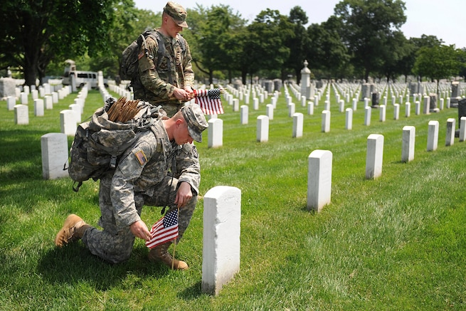 "Soldiers pay their respects after placing a small American flag in front of a headstone during ""Flags In,"" an annual event before Memorial Day honoring our nation's fallen service members at Arlington National Cemetery in Arlington, Va., May 26, 2016. DoD photo by Marvin D. Lynchard"