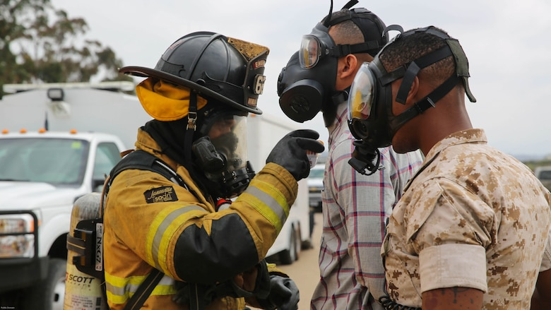 A firefighter with the Marine Corps Air Station Miramar Fire Department decontaminates a suspect and a military police officer with the Provost Marshal's Office during a Chemical, Biological, Radiological, Nuclear and High-Yield Explosives exercise at the gas chamber aboard Marine Corps Air Station Miramar, Calif., May 18, 2016. The exercise revolved around PMO, the Miramar Fire Department, Explosive Ordnance Disposal, and Aircraft Rescue and Firefighting working together to identify and eliminate the threat of a simulated clandestine drug lab.