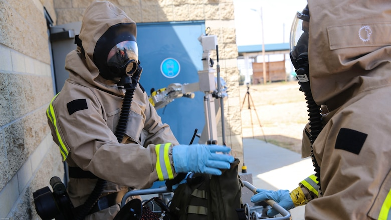 Marines with Explosive Ordnance Disposal gather their gear before entering the hazardous area during a Chemical, Biological, Radiological, Nuclear and High-Yield Explosives exercise at the gas chamber aboard Marine Corps Air Station Miramar, Calif., May 18, 2016. The exercise revolved around PMO, the Miramar Fire Department, Explosive Ordnance Disposal, and Aircraft Rescue and Firefighting working together to identify and eliminate the threat of a simulated clandestine drug lab.