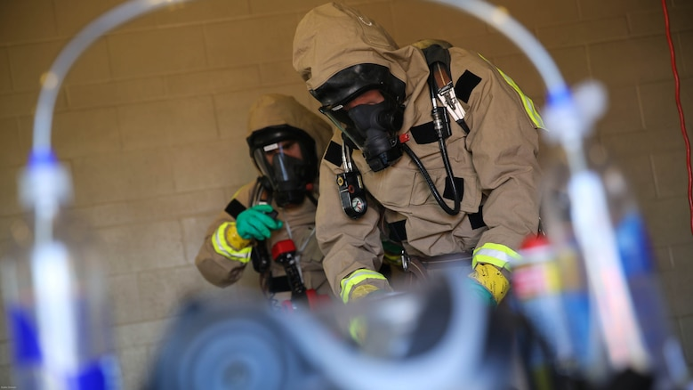 Marines with the Aircraft Rescue and Firefighting hazardous material team assess the contaminated area during a Chemical, Biological, Radiological, Nuclear and High-Yield Explosives exercise at the gas chamber aboard Marine Corps Air Station Miramar, Calif., May 18, 2016. The exercise revolved around PMO, the Miramar Fire Department, Explosive Ordnance Disposal, and Aircraft Rescue and Firefighting working together to identify and eliminate the threat of a simulated clandestine drug lab.