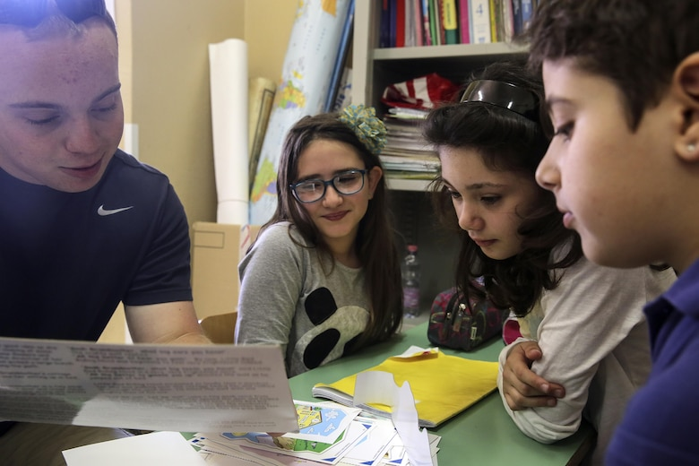 RPSA Alexander Varner, a religious program specialist with Special Purpose Marine-Air Ground Task Force Crisis Response-Africa, reads a book to children at 3rd Circolo Didattico ''Giovanni Paolo II'' Gravina Di Catania, Italy, May 18, 2016.  The Marines and sailors interacted with the children, going over some English for an upcoming test, as well as creating and participating in games during the children's recess period. (U.S. Marine Corps photo by Cpl. Alexander Mitchell/released)