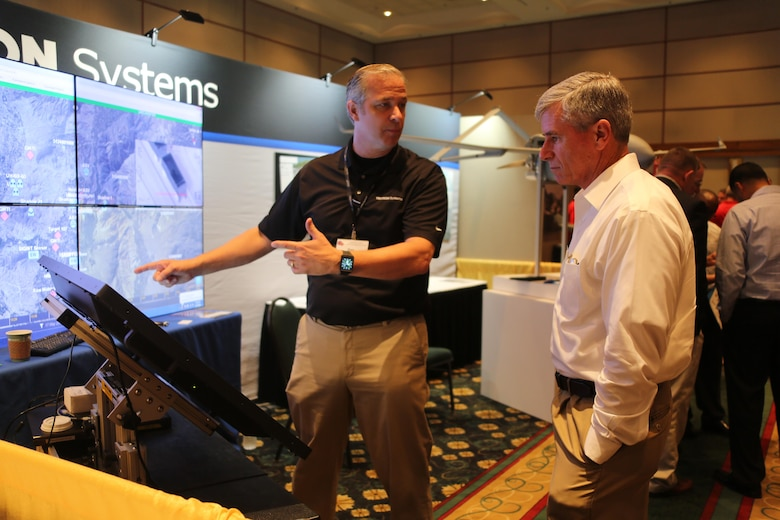 Ken Phillips,left, showcases an exhibit during the 45th Annual Marine Corps Aviation Association Symposium and Marine Aviation Summit at New Bern, N.C., May 17, 2016. Hundreds of naval aviators gathered at the convention center for the opening brief to the weeklong event. Senior leaders gathered to discuss the future of Marine Corps aviation and the steps the Corps is taking to reach its set goals. Phillips is a manager with Textron Systems. (U.S. Marine Corps photo by Cpl. N.W. Huertas/Released)
