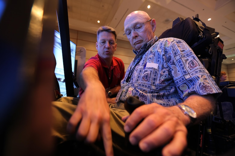 Mark Bosley, left, explains the controls of the Lockheed Martin  F-35 demonstrator to John Hudson during the 45th Annual Marine Corps Aviation Association Symposium and Marine Aviation Summit at New Bern, N.C., May 17, 2016. Hundreds of naval aviators gathered at the convention center for the opening brief to the weeklong event. Senior leaders gathered to discuss the future of Marine Corps aviation and the steps the Corps is taking to reach its set goals. Bosley is a Lockheed Martin F-35 demonstrator instructor pilot and Hudson is a retired U.S. Marine and award nominee at the event. (U.S. Marine Corps photo by Cpl. N.W. Huertas/Released)