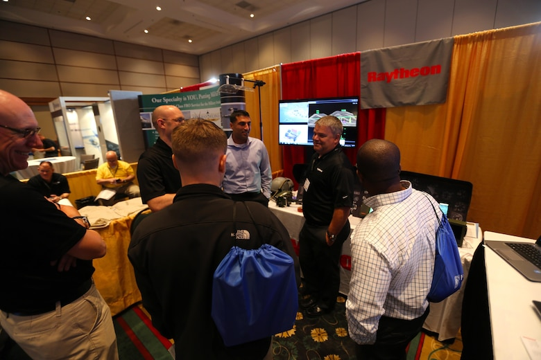 Attendees interact with exhibits during the 45th Annual Marine Corps Aviation Association Symposium and Marine Aviation Summit at New Bern, N.C., May 17, 2016. Hundreds of naval aviators gathered at the convention center for the opening brief to the weeklong event. Senior leaders gathered to discuss the future of Marine Corps aviation and the steps the Corps is taking to reach its set goals. (U.S. Marine Corps photo by Cpl. N.W. Huertas/Released)