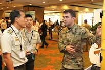 Army 1st Lt. Christopher J. Collins, a platoon leader with the 25th Infantry Division's Lightning Academy, discusses the academy's functions with officers from Singapore during the fourth annual Land Forces Pacific Symposium and Exhibition held in Honolulu, May 25, 2016. Army photo by, Staff Sgt. Brandon C. McIntosh