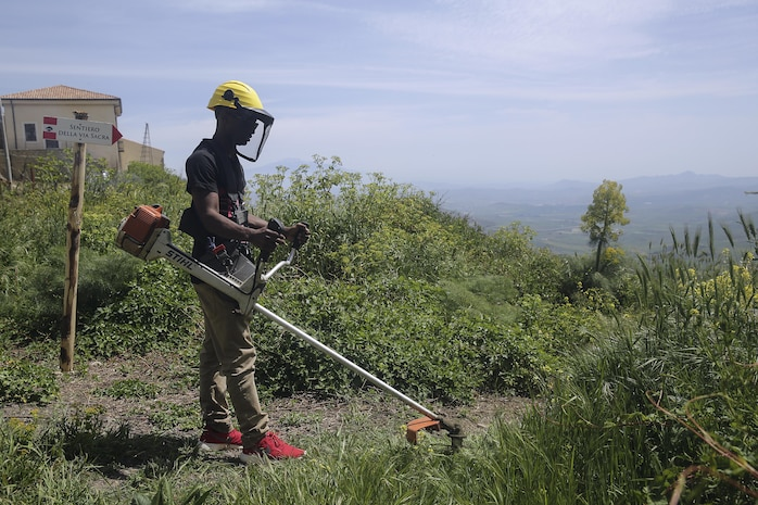Cpl. Chris Pittman, a motor transport Marine with Special Purpose Marine Air-Ground Task Force Crisis Response-Africa Logistics Combat Element, cuts grass and overgrowth at Castello di Lombardia in Enna, Sicily, on April 22, 2016, during a community relations project.  The Marines and sailors cleaned up garbage and debris on the castle grounds so the community can enjoy its beauty and landscape.  (U.S. Marine Corps photo by Cpl. Alexander Mitchell/released)