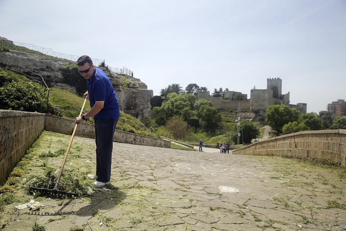 Lt. Arthur Briggs, the chaplain with Special Purpose Marine Air-Ground Task Force Crisis Response-Africa Logistics Combat Element, rakes up garbage and debris at Castello di Lombardia in Enna, Sicily, during a community relations project on April 22, 2016.  Marines assist local areas in various projects to build relationships with the Sicilian government and people.  (U.S. Marine Corps photo by Cpl. Alexander Mitchell/released)