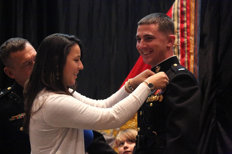 A Marine Corps aviator is pinned by his wife during a winging ceremony at New Bern, N.C., May 19, 2016. Naval aviators received the prestigious honor of receiving an iconic emblem, depicting the culmination of years of training, perseverance and sacrifice. Pilots and crewmen receive wings once they complete their respective training requirements and are then designated to join the fleet as an operational Marine Corps asset. The winging ceremony took place during the 45th Annual Marine Corps Aviation Association Symposium and Marine Corps Aviation Summit. (U.S. Marine Corps photo by Cpl. N.W. Huertas/ Released)
