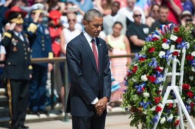 President Barack Obama bowing his head after laying a wreath at the Tomb of the Unknown Soldier.