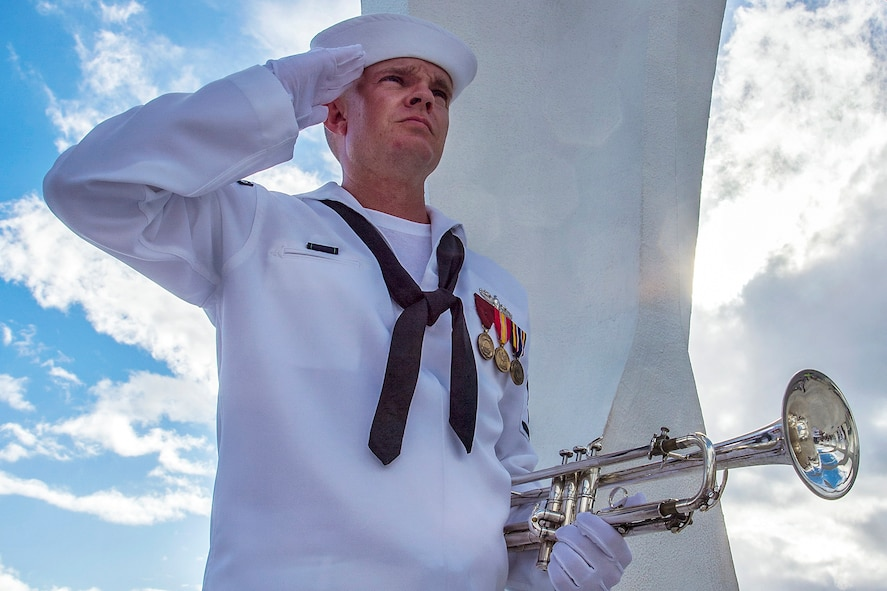 Navy Petty Officer 3rd Class Shelby Tucci, assigned to the Pacific Fleet Band, saluting after playing taps.