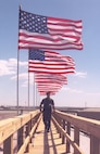 A service member walks under displayed American flags at the Pentagon in Washington, D.C., during a 9/11 observance in 2002. (Courtesy photo)