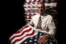 Army veteran Alvin Nieder poses with the flags that he and his team will raise outside the Pentagon in Washington, D.C., in honor of Memorial Day. Nieder has volunteered to organize this flag raising event since 2002. (U.S. Air Force photo/Staff Sgt. Alyssa Gibson)