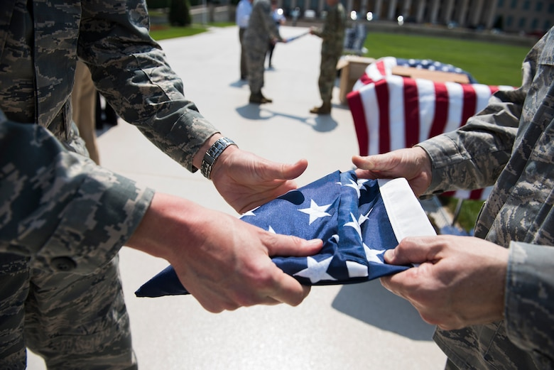 Maj. Andrew Nye, left, and Maj. James Hogan fold an American flag in honor of Memorial Day outside of the Pentagon in Washington, D.C., May 25, 2016. (U.S. Air Force photo/Staff Sgt. Alyssa Gibson)