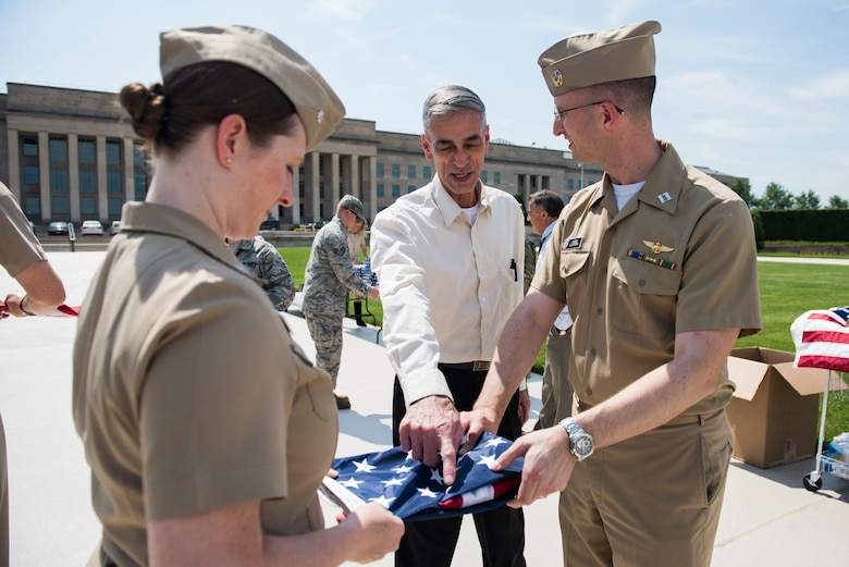 Navy Lt. Christopher Lawson gets instructions from Army veteran Alvin Nieder on how to properly fold a flag during a flag-raising event that Nieder has organized in honor of Memorial Day outside of the Pentagon in Washington, D.C., May 25, 2016. (U.S. Air Force photo/Staff Sgt. Alyssa Gibson)
