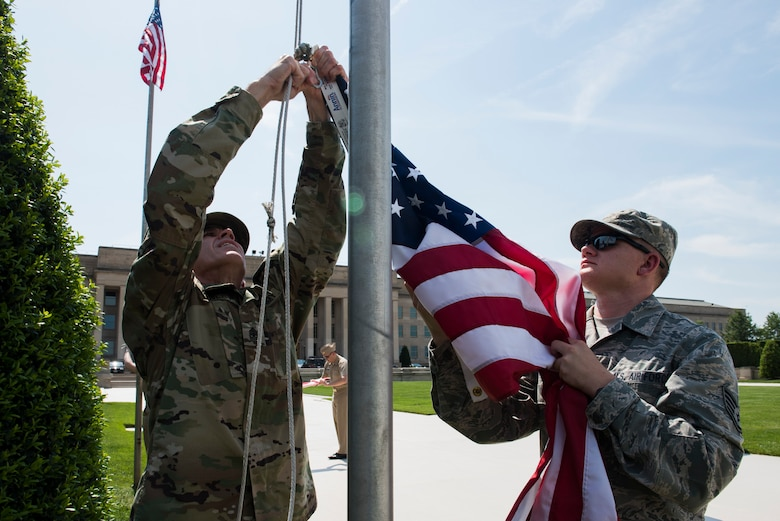 Army Sgt. Maj. Tim Wagley, left, and Air Force Staff Sgt. Bryan Payton raise a flag in honor of Memorial Day outside of the Pentagon in Washington, D.C., May 25, 2016. (U.S. Air Force photo/Staff Sgt. Alyssa Gibson)