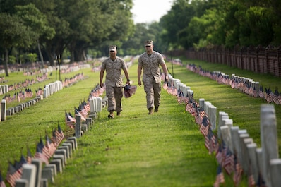 Sgt. Moises Alaniz and Cpl. Joshua Hernandez, Marines from Marine Corps Support Facility New Orleans, walk in between the tombstones of fallen service members during a Memorial Day volunteer event at Chalmette National Cemetery in Chalmette, La., May 27, 2016. The National Park was built on the grounds of the Battle of New Orleans which took place at the end of the War of 1812.  It is now the final resting place for over 15,300 veterans of American military campaigns from the Civil War to the Vietnam War. (U.S. Marine Corps photo by Lance Cpl. Devan A. Barnett)