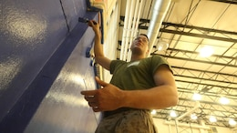 Cpl. Austin Richards, a flight equipment technician with Marine Medium Tiltrotor Squadron 261, paints the gymnasium of the Graham Windham's Manhattanville Cornerstone Community Center in Manhattan, New York, May 27, 2016. The Marines are visiting the city to interact with the public, demonstrate capabilities and teach the people of New York about America's sea services.