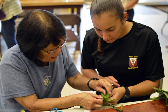 Linda Hirano, left, a Wahiawa Rainbow Seniors volunteer, helps Army Pfc. Vanessa Sheika make a lei in Honolulu, May 27, 2016. Soldiers teamed with the senior citizens group to make nearly 1,900 leis to place on headstones at the Schofield Barracks Post Cemetery for Memorial Day. Army photo by Staff Sgt. Armando R Limon