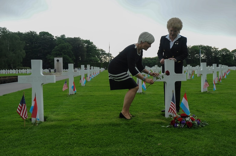 """Helen Patton, granddaughter of U.S. Army Gen. George S. Patton, left, places a rose at the gravesite of U.S. Army Air Corps 1st Lt. Hanford """"Rusty"""" J. Rustand, a B-17 bomber pilot killed in World War II, as Marilynn Rustand Lieurance, Rustand's daughter, watches after a Memorial Day ceremony at the Luxembourg American Cemetery and Memorial in Luxembourg, May 28, 2016. Rustand died when his B-17 came under enemy fire during a mission near Merseburg, Germany, and crashed on Nov. 2, 1944, nearly half a year before Lieurance was born. Both Rustand and Patton's grandfather are among the 5,076 American service members buried at the cemetery. (U.S. Air Force photo by Staff Sgt. Joe W. McFadden/Released)"""