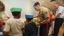 Cpl. William Linke, a rifleman with 3rd Battalion, 6th Marine Regiment, helps children build care packages during an effort to bring aid and support to children in need at Times Square Church in New York, May 28, 2016. Fleet Week New York is an opportunity for the public to interact with service members from America's sea services, spreading awareness of the Navy and Marine Corps' missions at home and abroad.