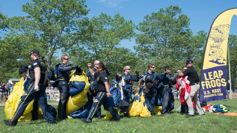 Members of the U.S. Navy Parachute Team, or the Leap Frogs, congratulate one another after an aerial parachute demonstration during Military Day as part of Fleet Week at Eisenhower Park in East Meadow, New York, May 28, 2016. The Marines and sailors are visiting to interact with the public, demonstrate capabilities and teach the people of New York about America's sea services.
