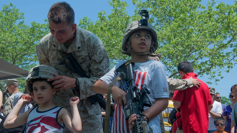 Cpl. Joseph Binari, a rifleman with 3rd Battalion, 6th Marine Regiment, helps a local child try on a Marine helmet during Military Day as part of Fleet Week at Eisenhower Park in East Meadow, New York, May 28, 2016. The Marines and sailors are visiting to interact with the public, demonstrate capabilities and teach the people of New York about America's sea services.