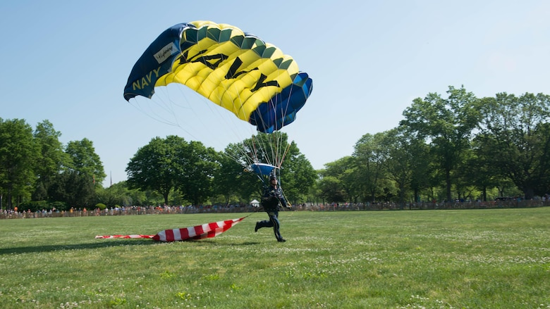 A member of the U.S. Navy Parachute Team, or the Leap Frogs, performs an aerial parachute demonstration during Military Day as part of Fleet Week at Eisenhower Park in East Meadow, New York, May 28, 2016. The Marines and sailors are visiting to interact with the public, demonstrate capabilities and teach the people of New York about America's sea services.