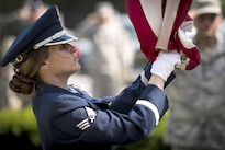 Air Force Senior Airman Tiffany Fogel reaches to secure an American flag as it is lowered during a retreat ceremony to commemorate Memorial Day at Joint Base Andrews, Md., May 26, 2016. Fogel is an administrative assistant and resource advisor assigned to the 99th Airlift Squadron. Air Force photo by Senior Master Sgt. Kevin Wallace