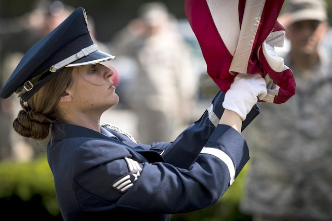 Air Force Senior Airman Tiffany Fogel secures an American flag as it is lowered during a retreat ceremony honoring Memorial Day at Joint Base Andrews, Md., May 26, 2016. Fogel is an administrative assistant and resource advisor assigned to the 99th Airlift Squadron. Air Force photo by Senior Master Sgt. Kevin Wallace