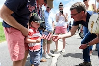 Defense Secretary Ash Carter gives one of his coins to a young bystander attending the Rolling Thunder demonstration ride at the Pentagon's north parking lot, May 29, 2016. DoD photo by Army Sgt. 1st Class Clydell Kinchen