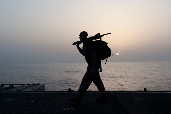 A Marine participates in a ruck march honoring fallen service members at sunrise on the flight deck of the USS Boxer in the Gulf of Aden, May 28, 2016. Navy photo by Seaman Eric Burgett