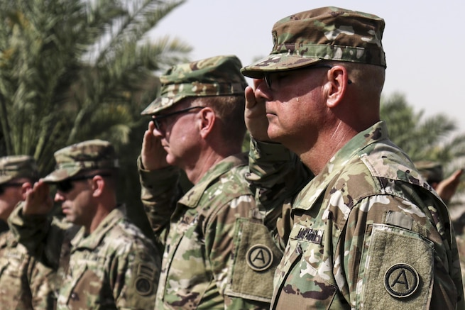 Soldiers salute the flag during the Memorial Day service the U.S. Army Central and Area Support Group-Kuwait hosted at Camp Arifian, Kuwait, May 30, 2016. The ceremony brings the Camp Arifian community together to honor fallen service members.