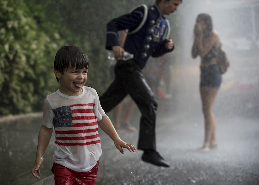 A group of children and teenagers play under the water spray from a fire truck at the end of the route of the 2016 National Memorial Day Parade in Washington, D.C., May 30. U.S. Army Reserve Soldiers marched in the parade, represented by the 200th Military Police Command, from Fort Meade, Maryland; the 55th Sustainment Brigade, from Fort Belvoir, Virginia; and the Military Intelligence Readiness Command, from Fort Belvoir. (U.S. Army photo by Master Sgt. Michel Sauret)