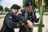 Spc. Amber Wardell, U.S. Army Reserve Soldier with the 400th Military Police Battalion, from Fort Meade, Maryland, helps Sgt. Brittany Albanese, with the 443rd MP Company, adjust her flag carrier harness prior to marching in the 2016 National Memorial Day Parade in Washington, D.C., May 30. The U.S. Army Reserve was represented by Soldiers from the 200th Military Police Command, from Fort Meade, Maryland; the 55th Sustainment Brigade, from Fort Belvoir, Virginia; and the Military Intelligence Readiness Command, from Fort Belvoir. (U.S. Army photo by Master Sgt. Michel Sauret)