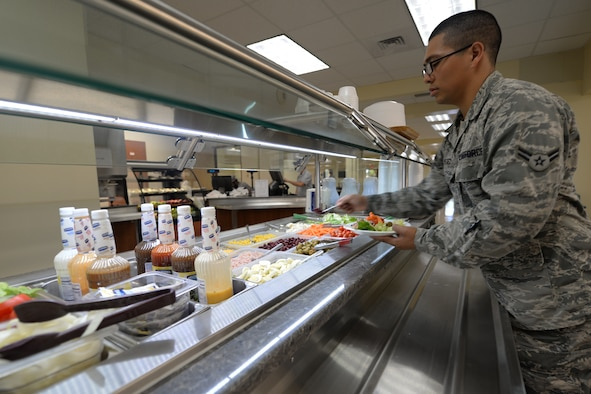 Airman 1st Class Mario Perez, 36th Force Support Squadron, makes a salad in the Magellan Inn Dining Facility May 31, 2016, at Andersen Air Force Base, Guam. The newly renovated dining facility offers improved serving lines, charging stations where customers can charge their electronic devices and more menu options for Airmen. (U.S. Air Force photo by Tech. Sgt. Richard Ebensberger)