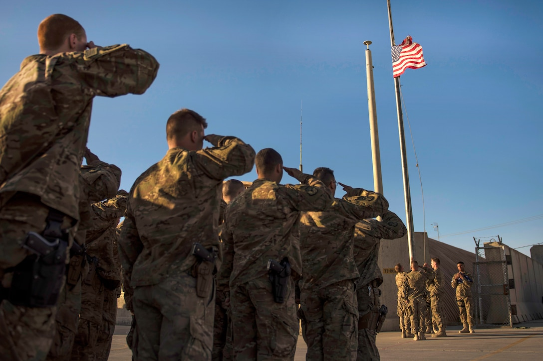 Airmen salute the lowering of a flag during a flag retirement ceremony at Bagram Airfield, Afghanistan, May 28, 2016. The airmen are assigned to the 455th Expeditionary Civil Engineer Squadron. The unit raised a new flag for Memorial Day events. Air Force photo by Senior Airman Justyn M. Freeman