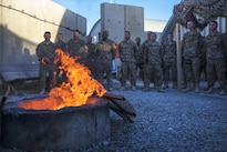 Airmen show respect while an old flag is burned during a flag retirement ceremony at Bagram Airfield, Afghanistan, May 28, 2016. Air Force photo by Senior Airman Justyn M. Freeman