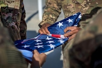 Members of the honor guard fold the flag during the Memorial Day remembrance ceremony at Bagram Airfield, Afghanistan, May 30, 2016. Air Force photo by Senior Airman Robert Dantzler