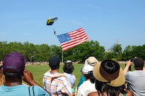 A sailor assigned to the Navy Parachute Team known as the Leap Frogs pulls the American flag while preparing to land at Eisenhower Park during Fleet Week New York in East Meadow, New York, May 28, 2016. Navy photo by Chief Mass Communication Specialist Travis Simmons