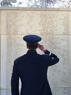 Senior Airman Colby Fahrenbacher, U.S. Air Forces in Europe Band member, salutes the name of his great-uncle at the North African American Cemetery in Tunisia, May 30, 2016. Fahrenbacher's great-uncle, Tech. Sgt. Merle Noffsinger was a B-24 gunner and bombardier who was shot down May 1, 1943. (U.S. Air Force photo by Staff Sgt. Will McCrary/Released).