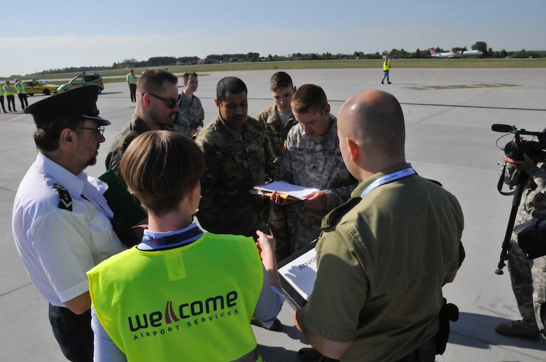 Polish forces, airport security, and U.S. Army Soldiers discuss procedures during the delivery of 20 Oklahoma National Guard Soldiers and equipment at the Gdańsk Lech Wałęsa Airport, May 25.