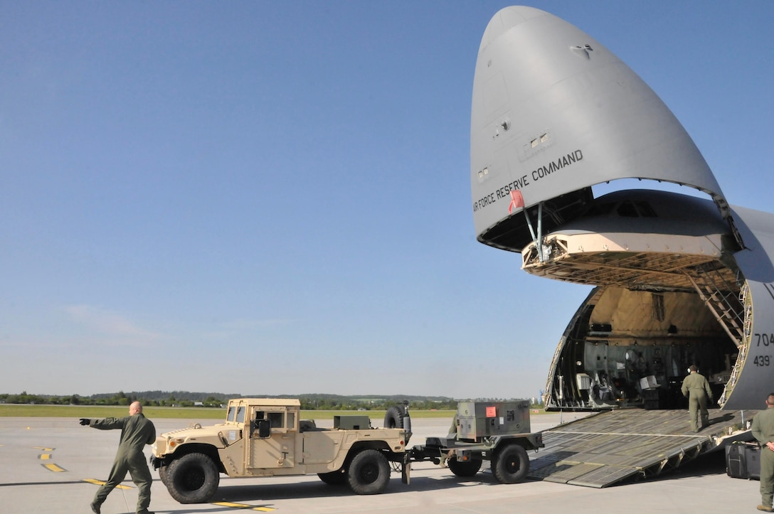 A 439th Airlift Wing Flight Crew member directs the unloading of a Humvee from a C-5 Galaxy at the Gdańsk Lech Wałęsa Airport in Poland, May 25.