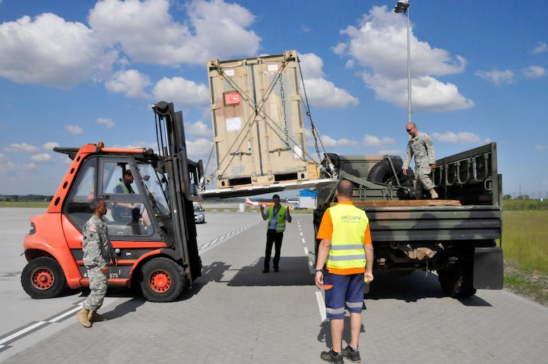 Polish Airport personnel at Gdańsk Lech Wałęsa Airport help the Oklahoma National guard with loading a pallet onto a Light Medium Tactical Vehicle, May 25.