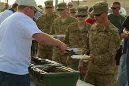 Soldiers of the 682nd Engineer Battalion, Minnesota National Guard and U.S. Army Central file through a serving line to receive steaks brought from Saint Paul, Minnesota, during a Feed Our Troops event at Camp Arifjan, Kuwait, May 15, 2016. Nearly 3,700 steak dinners were brought from Saint Paul, Minnesota, for Soldiers of the 682nd Engineer Bn., Minnesota National Guard and U.S. Army Central.