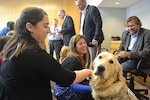 Defense Centers of Excellence staff members admire Lundy, a service dog, as his owner Jake Young, a former Navy SEAL, looks on. Photo courtesy of Defense Centers of Excellence for Psychological Health and Traumatic Brain Injury