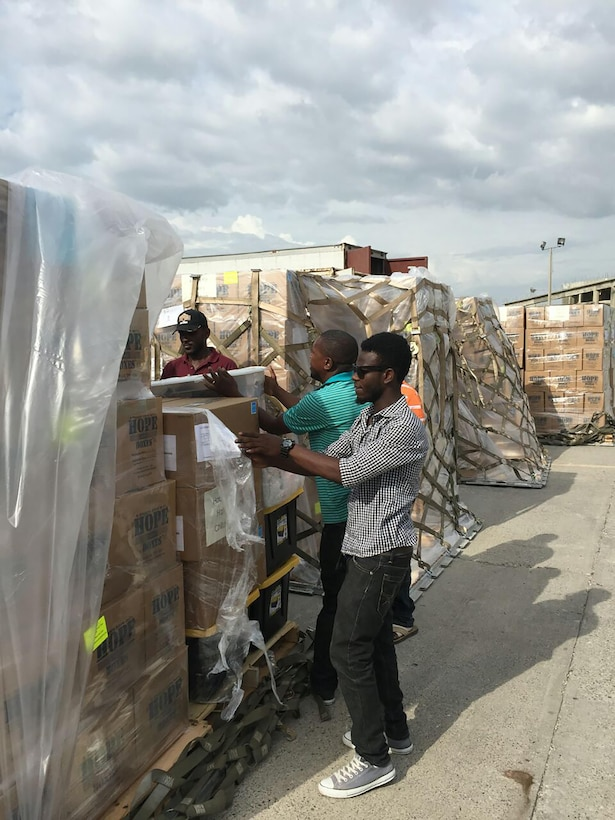 Pallets consisting of more than 100,000 pounds worth of rice and beans are unwrapped and being prepared to load onto trucks to be delivered to those in need in Haiti.
