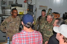 Staff Sgt. Robert Marshall (left), a machinist with 1109th Theatre Aviation Sustainment Maintenance Group, talks to Matthew Lillard (blue hat), Gen. Frank Grass (center), the chief of the National Guard Bureau, Robert Patrick (black shirt) and Jerrod Neimann (white hat) about helicopter parts he created on Camp Arifjan, Kuwait, May 18, 2016. This visit was part of the USO May Madness Tour.