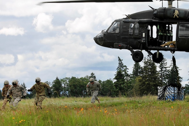 Soldiers rush away after hooking up cargo during slingload operations with a UH-60 Black Hawk helicopter at Joint Base Lewis McChord, Wash., May 20, 2016. Army photo by Capt. Tania Donovan